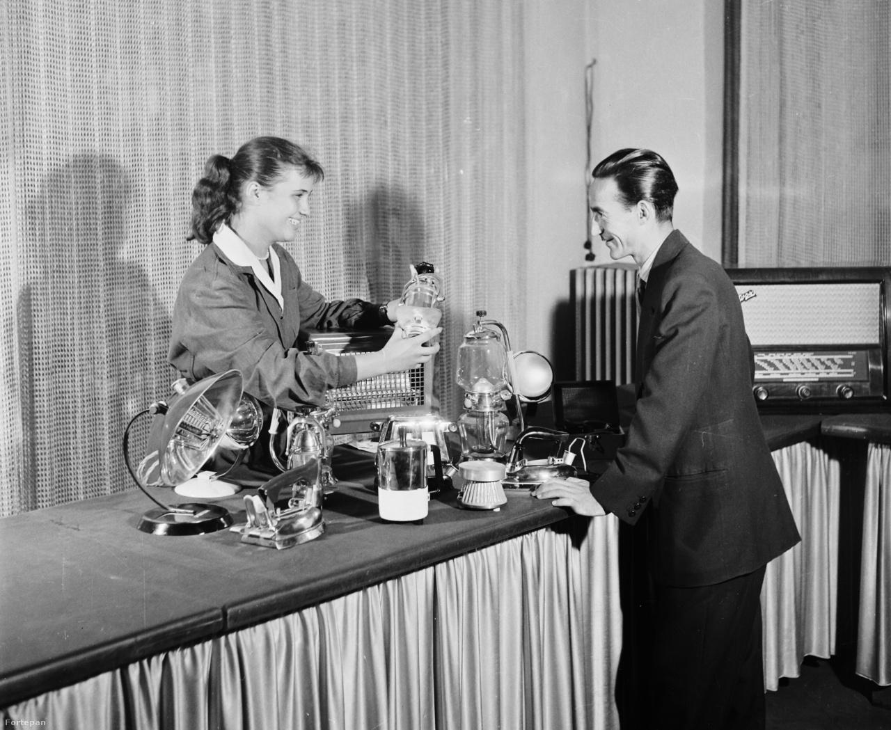 1958: Budapest V. Kossuth Lajos utca 2/b, KERAVILL üzlet, bemutatóterem. A spontán elkapott pillanatképen épp egy eladó a pultra fölhalmozott különféle műszaki cikkeket mutatja be egy vásárlónak. Láthatunk itt hősugárzót, többféle kávéfőzőt, vasalót, kenyérpirítót, a háttérben egy jókora rádiót.