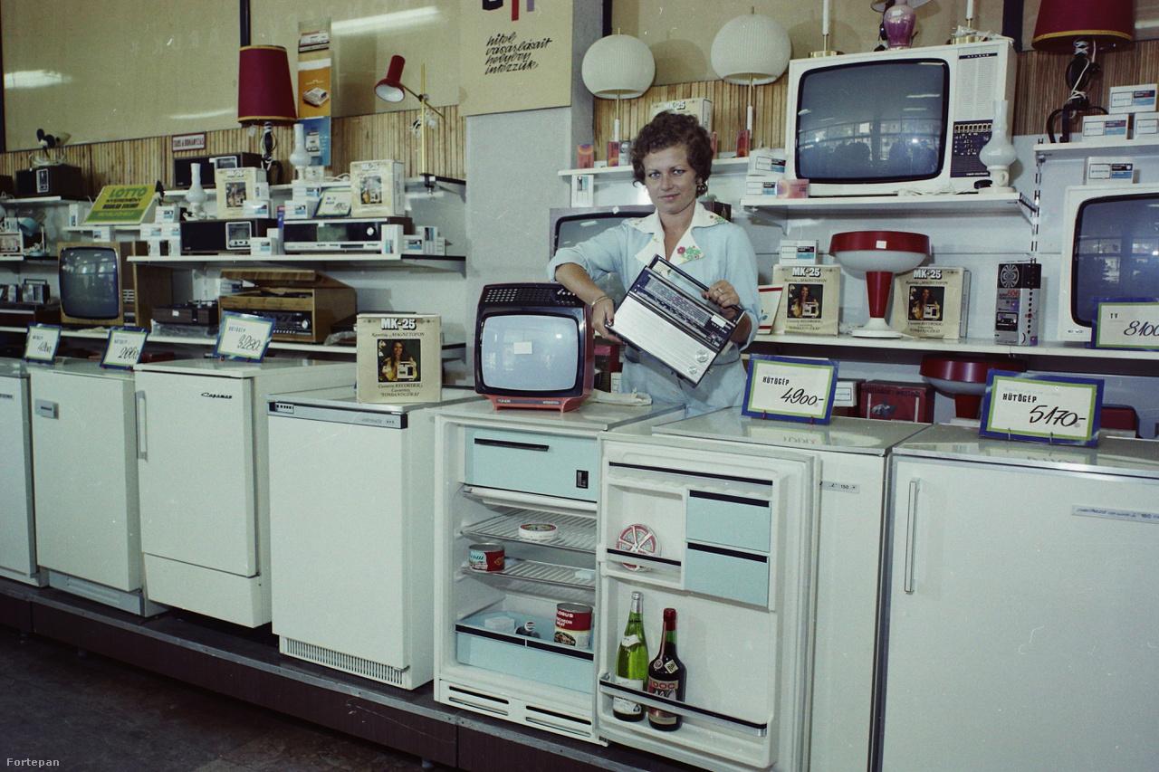 """1974: a gödöllői Szövetkezeti Áruház műszaki osztályának kínálata. A Szabadság téri háztartási boltban a hűtőszekrényeken, fagyasztógépeken kívül olyan alapvető szocialista műszaki cikkeket lehetett kapni, mint például a VEF táskarádió, BRG MK-25 kazettás magnó, Videoton TC 1607 """"Tünde"""" színes televízió. A hűtőben elhelyezett dekorációs termékek: Csárdás ömlesztett cikkelyes sajt, Globus löncshús, Pepsi-Cola, konzerv halászlé, fehér és vörös bor (Medoc, Kiváló Áruk Fóruma matricával)."""