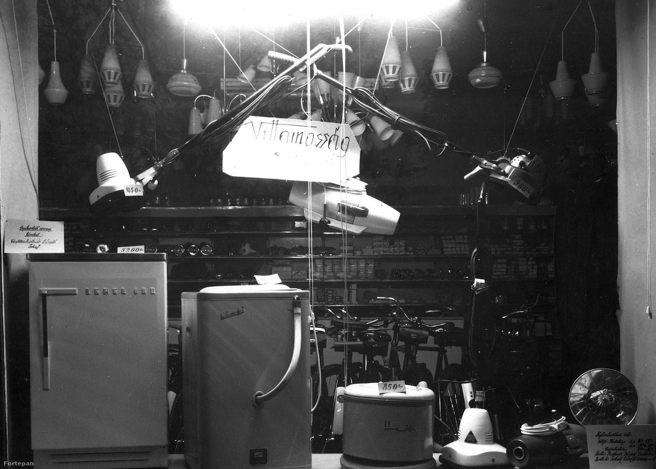 Egy dombóvári üzlet kissé kaotikus villamossági kirakata, 1964-ből. Van itt minden, Lehel 120 hűtőszekrény, Himfi mosógép (a Hajdúsági Iparművek terméke), centrifuga (szintén HIM), Raketa porszívó (szovjet gyártmány), többféle padlókefe, hősugárzó. A kirakat maga szakiskolai gyakorlati versenyre készült, egy tokaji diák műve.