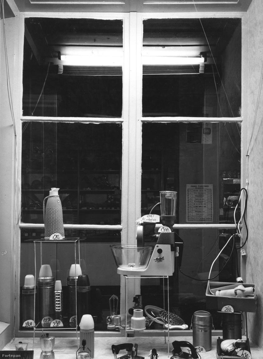 Háztartási bolt kirakata, többféle termosszal, kávéfőzővel, hajszárítóval, vasalóval, és középen, külön állványon üstökös (Komet) márkájú szovjet multifunkciós konyhai robotgéppel (1964).