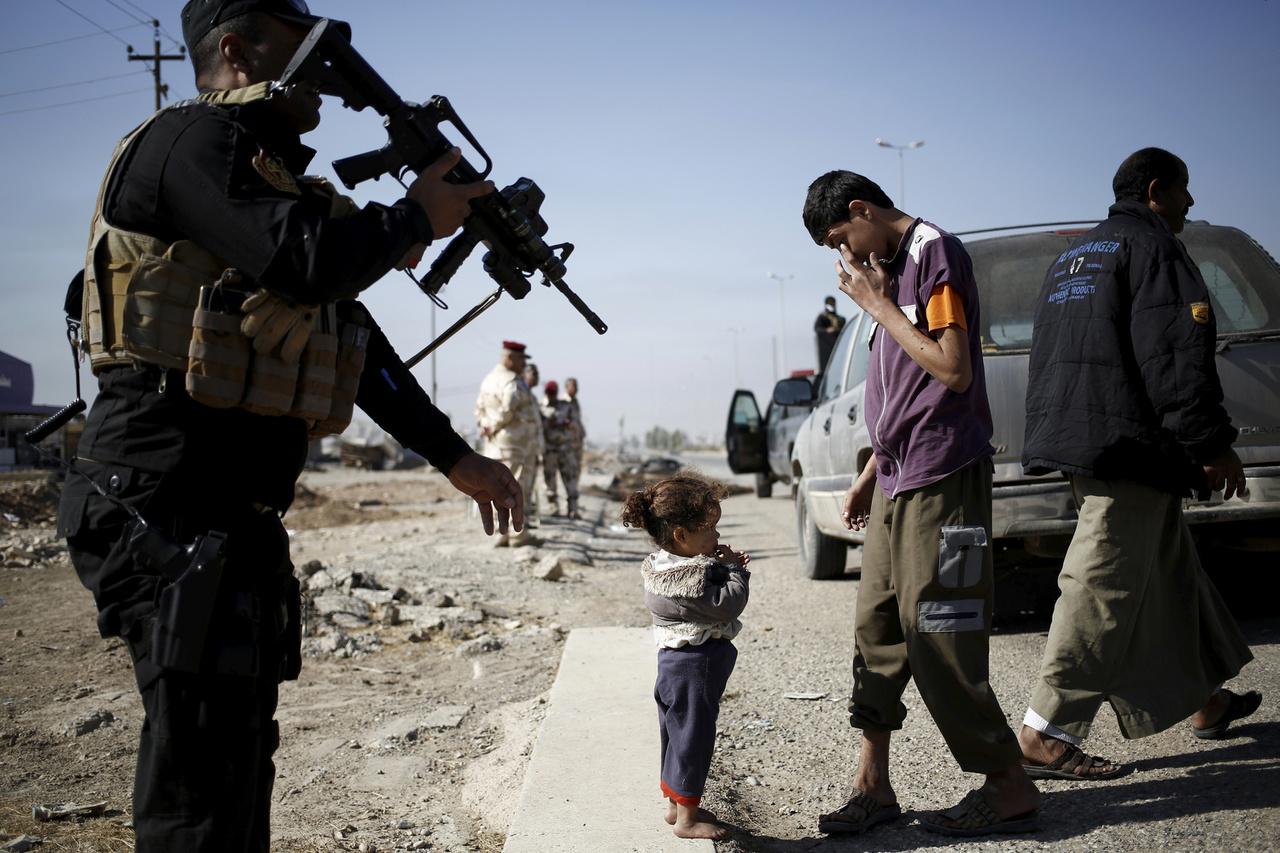Moszul, Irak, amit három év után, 2017 nyarán foglaltak vissza az Iszlám Államtól. Két gyereket ellenőriznek fegyveres katonák egy ellenőrzőpontnál a városba vezető (vagy onnan kivezető) úton.
