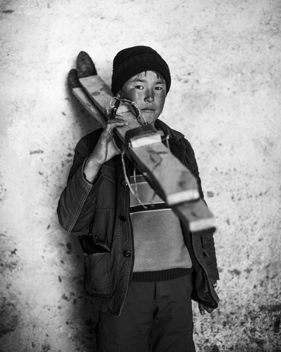 Afgán kisfiú házilag barkácsolt sílecekkel. 2009-ben egy segélyszervezet munkatársai mutatták meg a sportot a helyieknek a Fuladi-völgyben, azóta kedvelt téli szórakozássá vált a síelés a környéken.