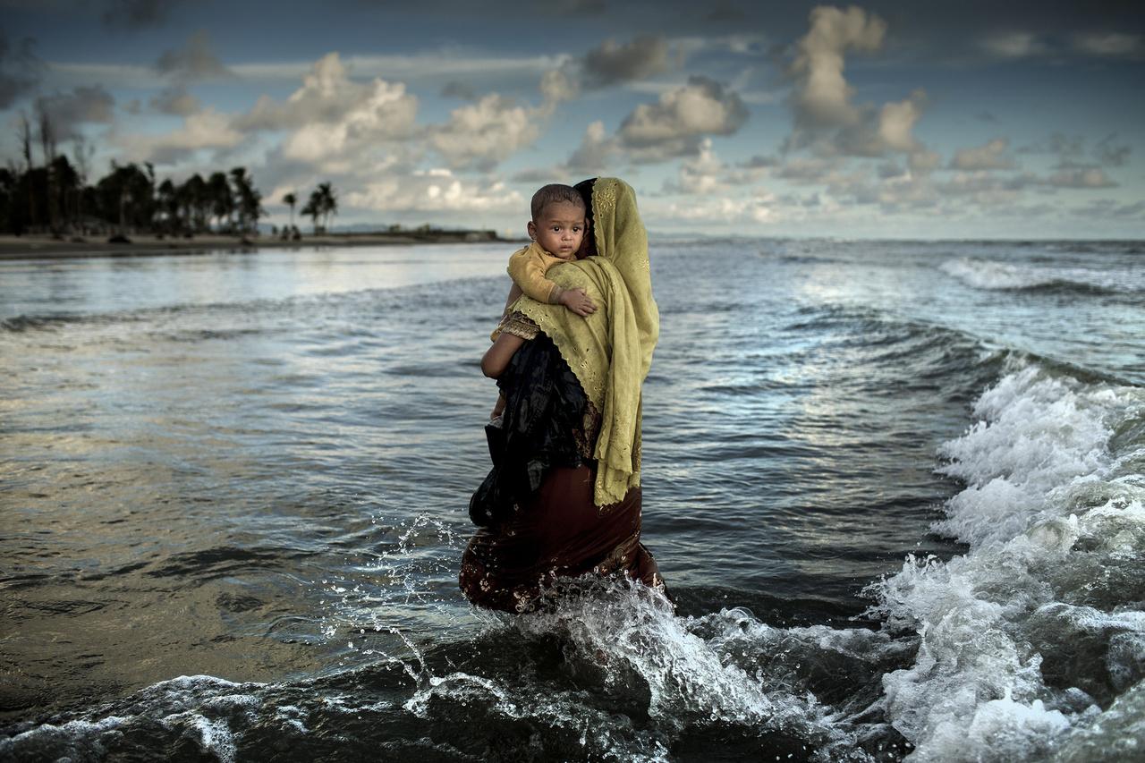 Anya és gyermeke sétál ki a vízből Bangladesben - ketten a több százezer rohingja menekültből, akik a népirtás elől menekültek a szomszédos Mianmarból. A hadsereg kegyetlenkedései nyomán legalább 320 ezer gyermek kényszerült elhagyni az otthonát.