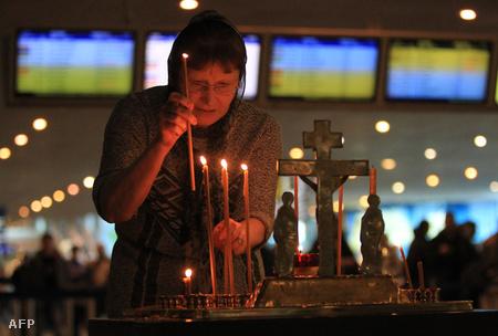 Egy asszony gyertyát gyújt az áldozatok emlékére