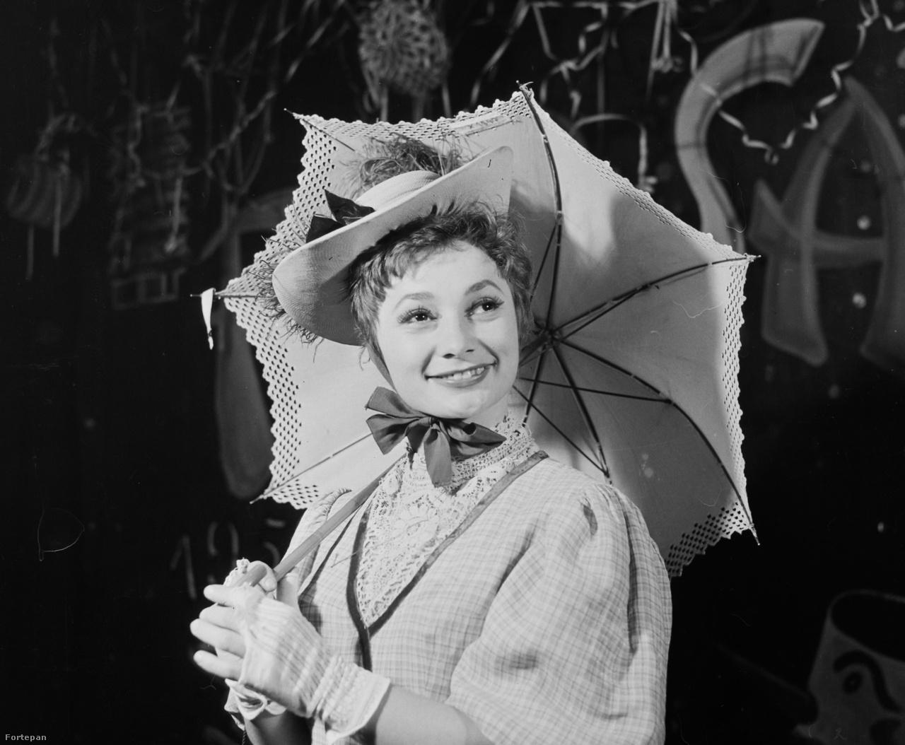 Végül a +1-es fotó, ahol nem a helyszínt, hanem a szereplőt szeretnénk                         azonosítani. A szerző itt is Bauer Sándor és tudjuk a helyszínt is, a Budapest                         Táncpalotában (Moulin Rouge) járunk a Nagymező utcában. De ki lehet a                         színésznő? Eddigi tippjeink Lechoczky Zsuzsa és Petress Zsuzsa voltak,                         de kifogott rajtunk a dolog. Ki lehet az esernyős lady?