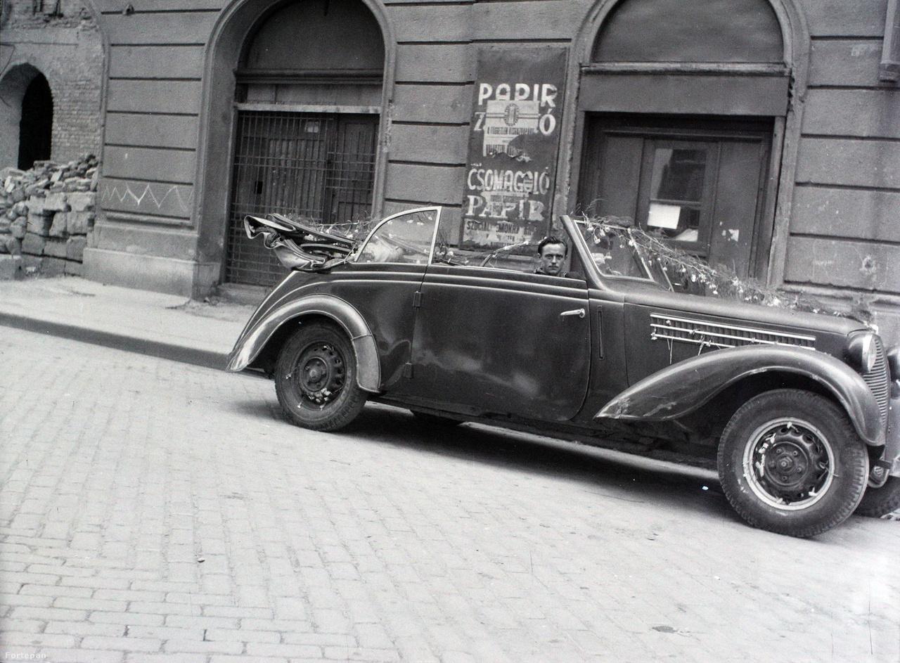 A szerző ismert, Hámori Gyula hivatásos fotós készítette a képet.                         Szinte biztos, hogy Budapesten járunk. Az autó láthatólag esküvői                         virágdíszítést kapott. Mivel a szerző rendszeresen fotózott zsidó                         esküvőkön, talán megkockáztathatjuk, hogy valahol a VII. kerületben,                         szűkebben talán a volt pesti Gettó környékén járunk. De hol?