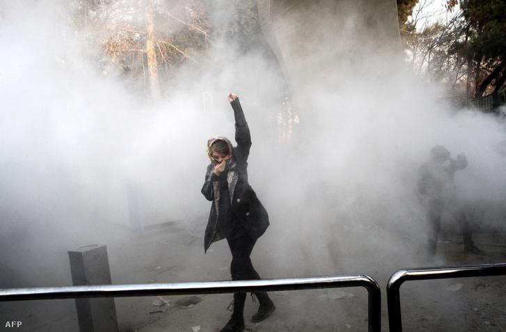 Könnygázfelhő gomolyog egy diák körül, aki a növekvő árak miatt tiltakozik társaival az iráni kormány ellen a Teheráni Egyetemnél