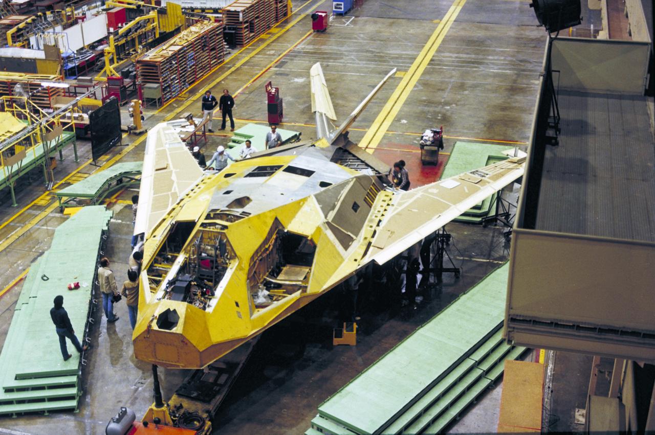 1980. Ez itt az első F-117 Nighthawk lopakodó repülőgép (légierő sorozatszáma: 79-10780) az összeszerelés utolsó fázisában, a Lockheed Skunk Works burbanki telephelyén. Első körben öt F-117-est építettek, amikkel a típus teljesítményét, stabilitását, irányíthatóságát és rendszereit tesztelték. A tesztgépeket a legnagyobb titokban, éjszaka vitték el C-5-ös szállítógépekkel a gyárból. Az első repülésre 1981. június 18-án került sor, de a lopakodók létezéséről 1988. november 10-ig nem lehetett tudni semmit. A képen látható repülőgép jelenleg a nevadai Nellis légibázison van kiállítva.