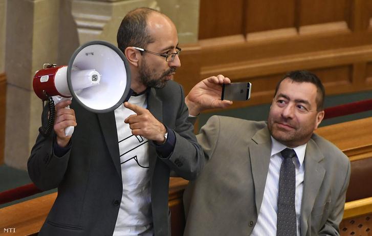Szabó Szabolcs független képviselő hangosbeszélővel a kezében a nemzeti felsőoktatásról szóló törvény módosításáról szóló javaslat szavazása előtt az Országgyûlés plenáris ülésén 2017. április 4-én. Jobbra Kónya Péter független képviselő.