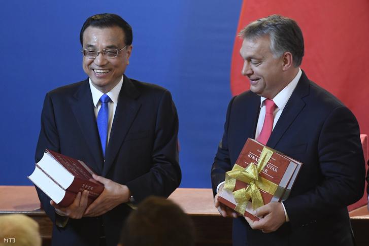 Orbán Viktor miniszterelnök (j) és Li Ko-csiang kínai kormányfő a magyar-kínai szótár köteteivel a tárgyalásukat követően tartott sajtótájékoztatón az Országházban 2017. november 28-án.