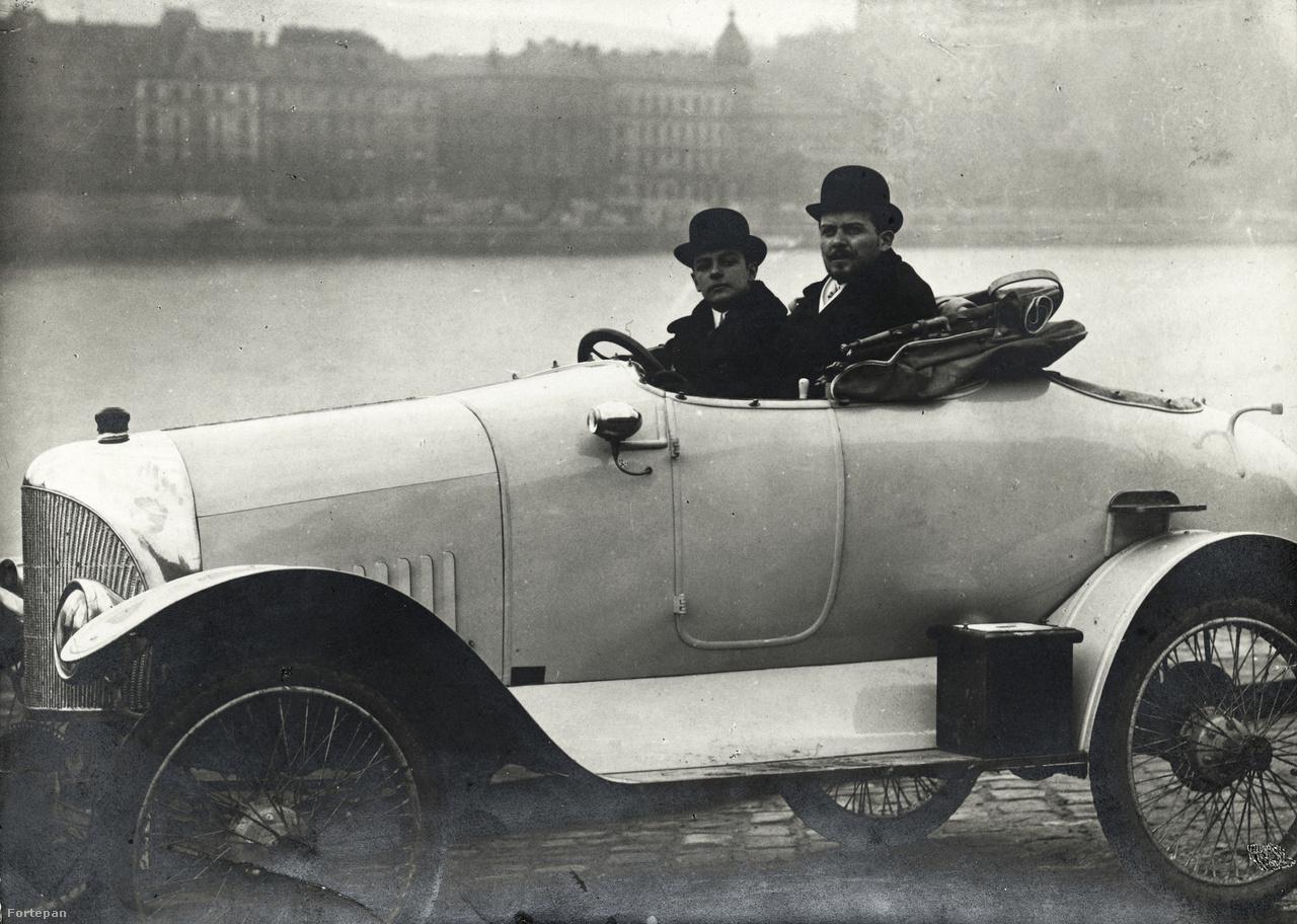 """Az első magyar autó-kiskocsi verseny (1912. VI. 5-8.) résztvevői. A képen egy 18/24 lóerős Ford látható, aminek karosszériáját valószínűleg Misura Mihály budapesti karosszériagyáros készítette. A volánnál: Vértessy Vilmos gépészmérnök, mellette az autó tulaja, Baráth Leó, a korszak ismert sportembere. """"Formájának karcsúságát még jobban kiemeli az elefántcsont színű fényezés és a tompított éllel bíró hűtő is, amely a berlini Windhoff-gyárban készült a tulajdonos útmutatása és Káposztás okl. mérnök rajza alapján, aki különben az egész kocsi összeállítója"""" – írta a Motor című szaklap az autóról. Baráth Leo László autója, amivel az 1913. októberében megtartott autós léghajóüldözésen is részt vett, valószínűleg az első világháborúban tűnt el. (Fotó: Berger Rezső, IV Kossuth Lajos u 1.)"""