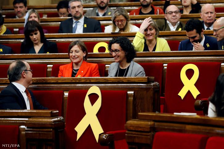 Carme Forcadell volt katalán házelnök (k balra) és Marta Rovira a függetlenségi Katalán Köztársasági Baloldal (ERC) párt főtitkára (k jobbra) az autonómiatörekvéseik miatt bebörtönzött katalán politikusok jelképévé vált sárga szalagokkal díszített székek közt a katalán regionális parlament alakuló ülésén Barcelonában 2018. január 17-én.