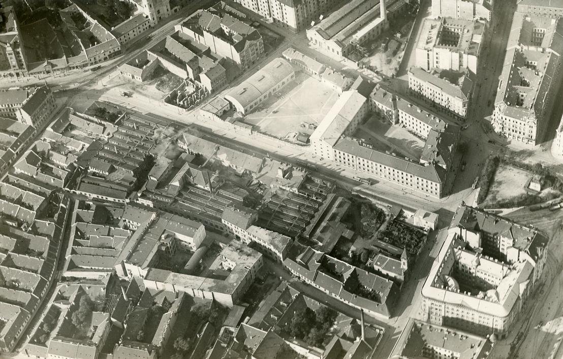 A kép felső részén, a kéményes épülettömb az egykori Pállfy-telep. Ezen a fotón a Fekete Sas utcára néző homlokzata látszik, amely ma is megvan (lásd lejjebb, az irodaházfotón).