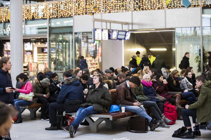 Utasok várakoznak vonatuk indulására az utrechti központi pályaudvaron 2018. január 18-án miután az erős szél miatt a holland vasúttársaság leállította a vonatközlekedést az egész országban.