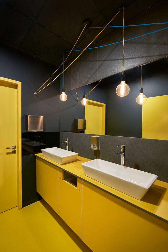 Jól mutat egymás mellett a sárga és a szürke a női mosdóban.
