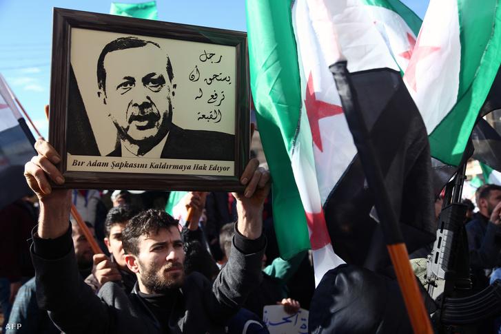 A török elnök képét emeli magasba egy törökök mellett tüntető szír férfi január 19-én, Azizban