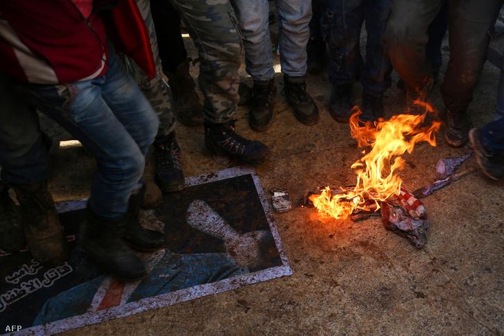 """Donald Trump amerikai elnök """"Gyilkos"""" feliratú képét tapossák és amerikai zászlót égetnek törökbarát szíriai tüntetők az észtak-szíriai Azizban, január 19-én"""