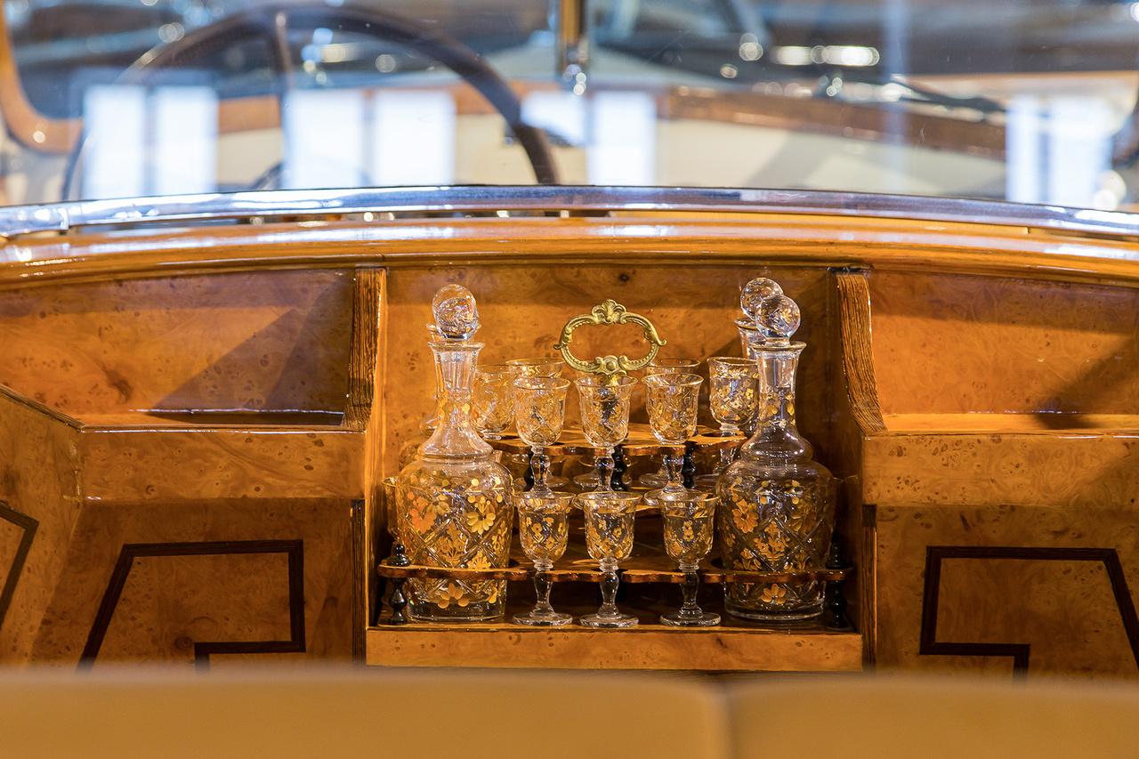 Packard Twelveben tombol a korabeli pompa, rózsafagyökér és kézzel festett kristálykészlet az úri közönségnek. Ezt a szettet simán el lehet képzelni egy süppedő bőrfoteles szivarszobában is.