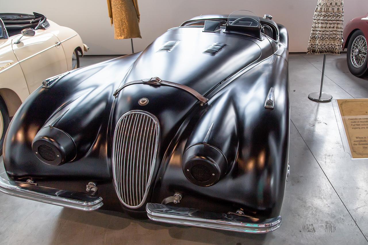 A Fekete Macska, Jaguar XK120 Roadster 1952-ből. 3500 ccm-es, 160 lóerős, hathengeres motorjával és formájával a Londoni autószalonon, 1948-ban tartott bemutatója után óriási sikervárományos volt, ám végül különböző nehézségek miatt a gyártás nehézségekbe ütközött. Mivel a várólista a típiusra két évnél is több volt, így csak a kor legnagyobb sztárjainak kiváltsága, mint Clark Gable-nek vagy Humphrey Bogart-nak volt esélye szerezni belőle egy-egy példányt.