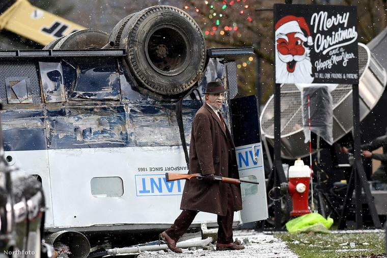 A maszkot viselő színész két társával együtt egy felborult járművet rabol ki.