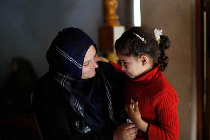 Neveen Barakat hatéves kislányát vigasztalja a Gázai övezetben.