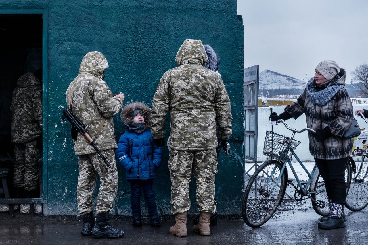 Egy gyereket ellenőriznek az ukrán katonák a kormányerők és a szakadárok által ellenőrzött terület határán. Az emberek kénytelenek akár egy teljes napot is a sorban állni, mielőtt átjuthatnak az ellenőrzőpontokon