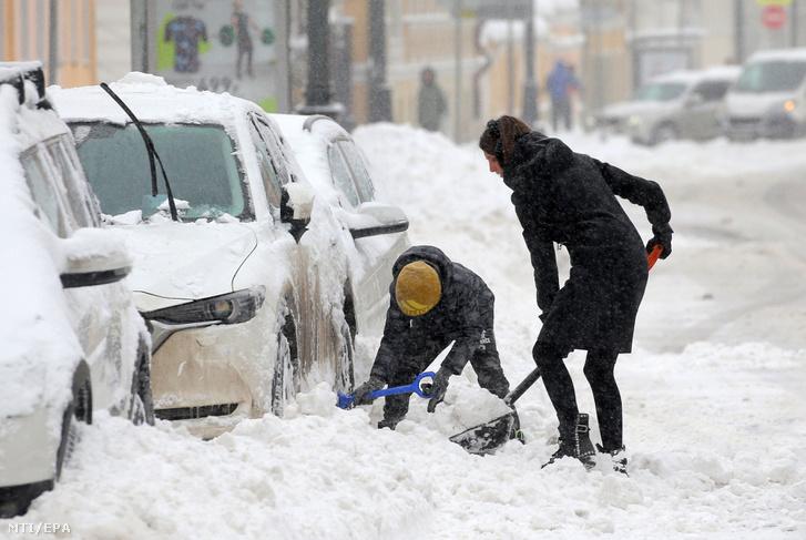 Havat lapátoló nők a sűrű hóesésben Moszkva belvárosában 2018. február 4-én. Példátlan mennyiségű hó hullott a hétvége során az orosz fővárosban, ami komoly közlekedési fennakadásokat és halálos balesetet okozott. A moszkvai repülőtereken szombaton 100, vasárnap pedig 85 járatot tartottak vissza vagy töröltek. A vonatok is késnek és fővárosi metró egyik vonalának felszíni szakaszán le kellett állítani a közlekedést, mert fa dőlt a pályára.