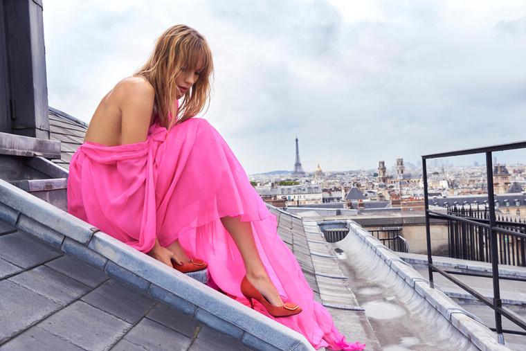A Roger Vivier modellje egy háztetőn gubbaszt rózsaszínben.