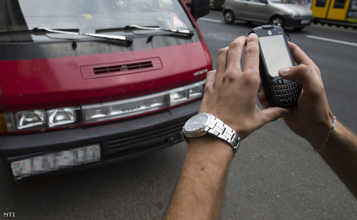 A Ferencvárosi Parkolási Kft. ellenőre egy parkoló autót rendszámát ellenőrzi hogy van-e érvényes parkolási engedélye a főváros IX. kerületében 2013. augusztus 21-én