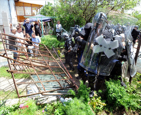 Rohamrendőrök nyomják be egy elárverezett családi ház kerítését 2010-ben Budafokon, miután jobbik országgyűlési képviselők és szimpatizánsok próbálják megakadályozni a kilakoltatást  (Fotó: Manek Attila)