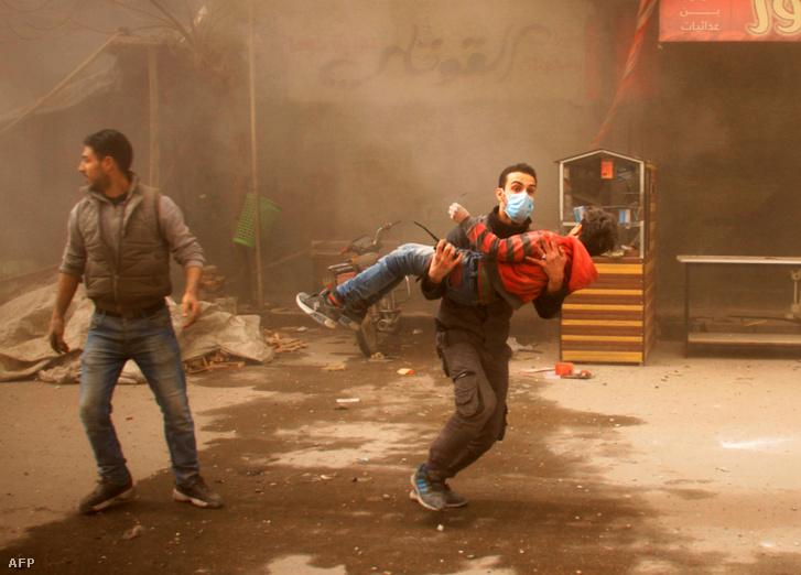 Sérült fiút cipel egy férfi a kormányerők légicsapása után Damaszkusz elővárosi régiójában.