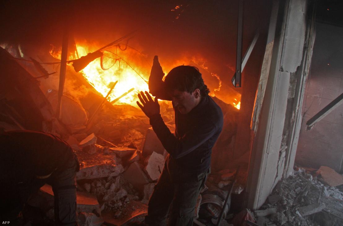 Szíriai férfi keres túlélőket egy lángoló ház romjai között, a kormányerők légicsapása után Damaszkusz elővárosában.