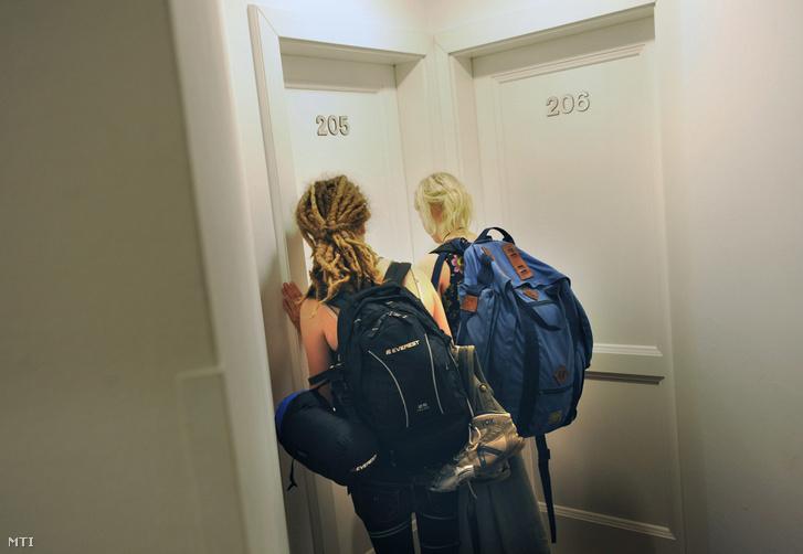 Hátizsákos turisták érkeznek egy VII. kerületi hostelben