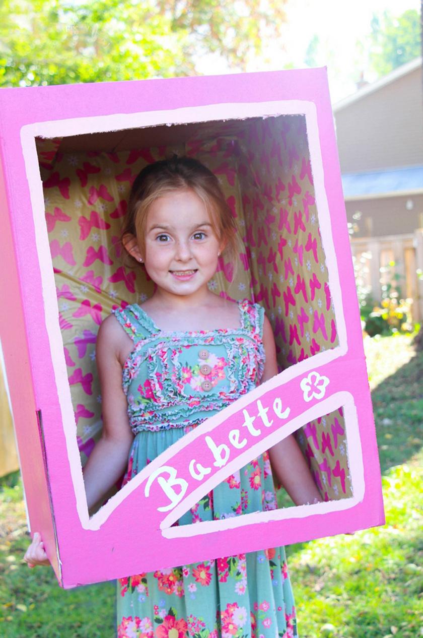 Egy jókora papírdobozt vonjatok be rózsaszín papírral, és vágjátok ki az elülső részét! Belülre ragasszatok vállpántokat! A kislányotok bújjon egy aranyos ruhácskába, és kész is a játékbabajelmez.