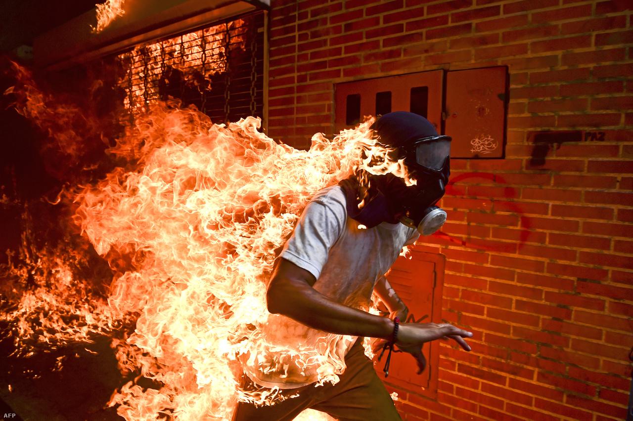 Venezuelai tüntetők csoportja kövekkel dobált egy felgyújtott rendőrmotort, amikor jármű üzemanyagtartálya felrobbant. A motor mellett álló tüntető ruhája lángra kapott, a körülötte állók pedig vízzel és rongyokkal próbálták eloltani. A néhány másodpercig tartó brutális jelenetet az AFP hírügynökség két fotósa is megörökítette. A képsorozatot tavaly az Indexen is láthatták.