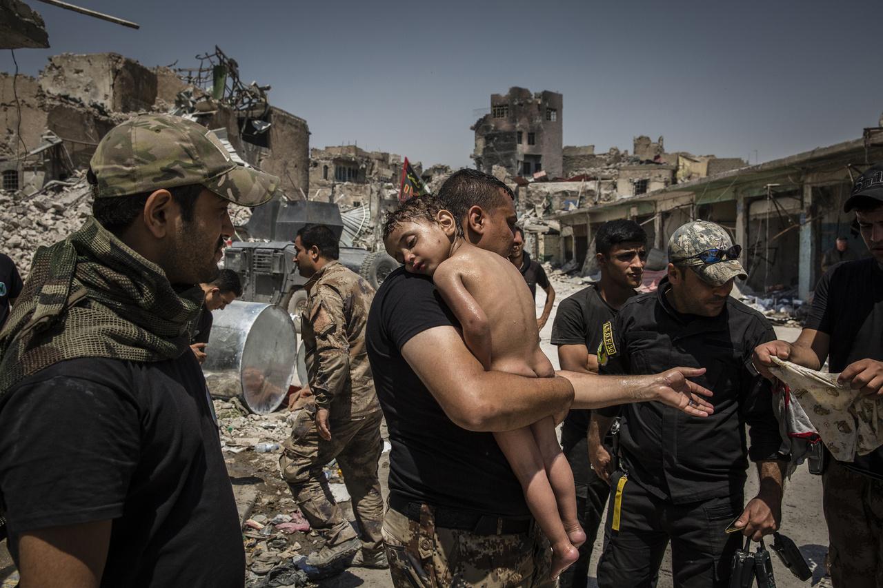 Egy ismeretlen fiút visz a kezében egy katona az ISIS által ellenőrzött Moszul óvárosában. A fiút egy férfi cipelte magával a város felszabadítására érkező iraki katonák felé, aki azt mondta, hogy az utcán találta a gyereket. A katonák szerint pajzsnak használta, mert egyedülálló férfiként könnyen válhatott volna célponttá az úton. A kisfiút végül egy iraki katona fogadta örökbe.