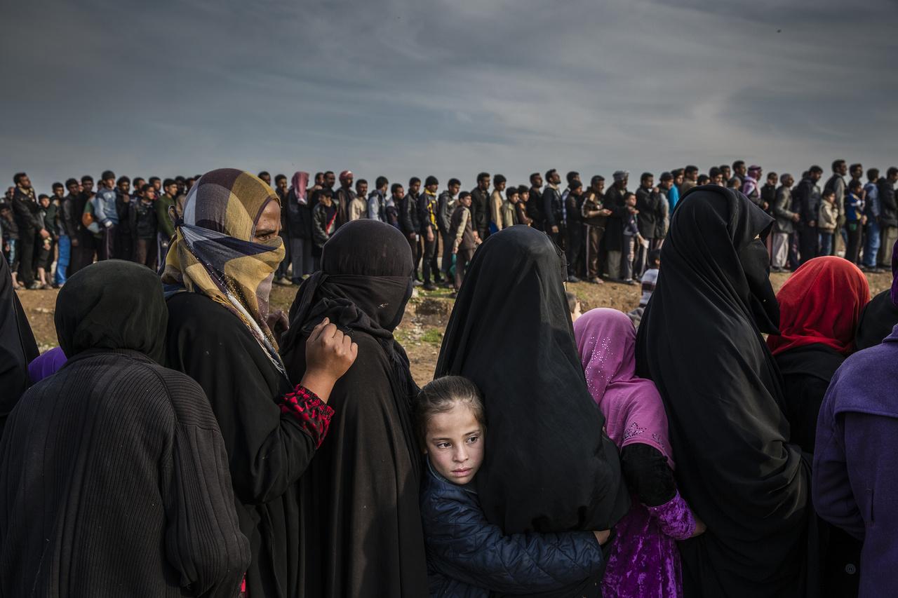 Moszulból menekülő civilek tömött sorokban várakoznak egy segélyszervezet elosztópontján, miután hónapokra a város utolsó, ostrom alá vont negyedében rekedtek. Voltak, akik a heves ostrom ellenére sem hagyták el otthonaikat, ők kizárólag a külföldről érkező segélyszállítmányok útján jutottak élelemhez, vízhez és bármihez.