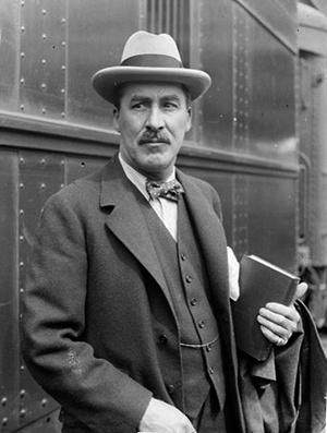 Howard Carter (archeológus) kezében egy könyvvel áll egy vonat mellett az állomáson 1924-ben, Chicagóban.