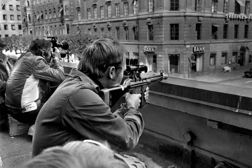 Fotósok és mesterlövészek guggolnak egymás mellett a norrmalmstorgi Sveriges Bankkal szemben.