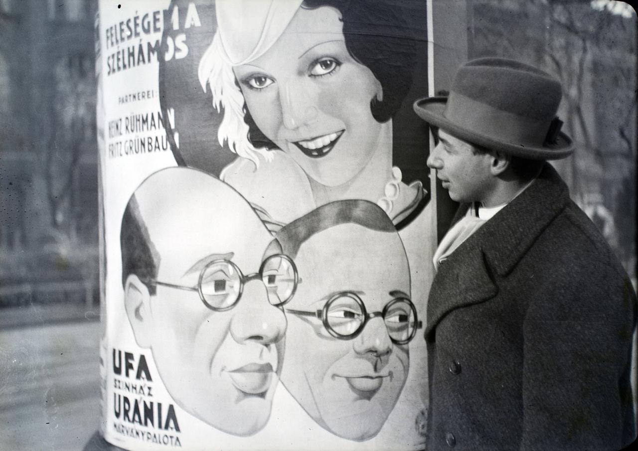 """Unger János, Feuerék egyik barátja a magyar mozikban 1931-ben bemutatott Feleségem a szélhámos című német film plakátja előtt. Nemcsak fotó maradt róla, hanem néhány mondat is az 1946-os levélben: """"És Unger Jancsi? Az, aki megfenyegetett, ha nem viszed haza a kocsiddal, akkor minden este express lapot küld neked kedves figyelmesség gyanánt, hogy éjjelente gondolj rá… hosszas munkaszolgálatoskodás után, akkor, mikor már csak kicsi kitartás kellett volna még, öngyilkos lett."""""""