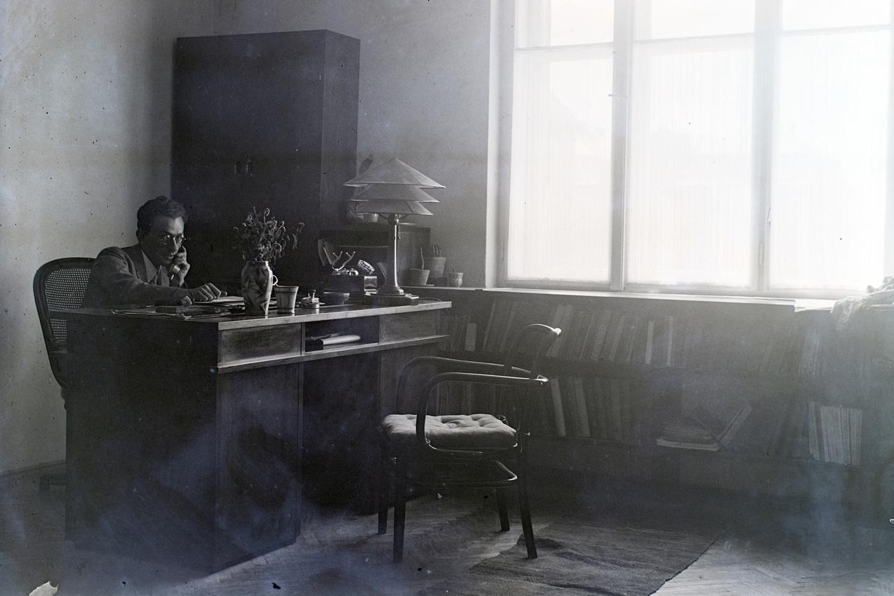 Az íróasztal mögött Feuer Gusztáv, valószínűleg első pesti lakásukban. A Fő utca 59. saját tervezésű berendezése vitte hírüket Budapesten. Ma lányuk, Feuer Helga dolgozik az íróasztalnál.