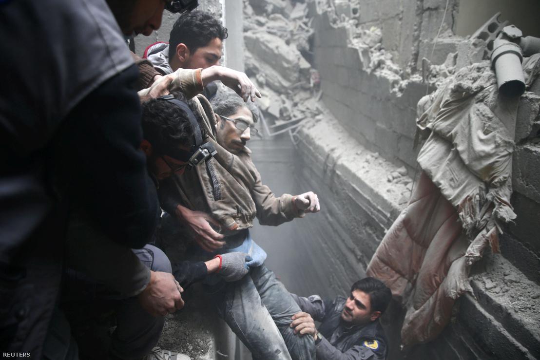 Sérült férfit emelnek ki a romok közül egy bombázás után Dumában.