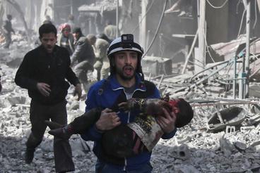 Gyereket cipel a kezében egy fehérsisakos  önkéntes mentő Hamúriában. Az ostrom alá vett térségbe nem jutnak el a nemzetközi segélyszervezetek, a hírügynökségek is a helyi civilek beszámolói alapján kapnak képet a történtekről.