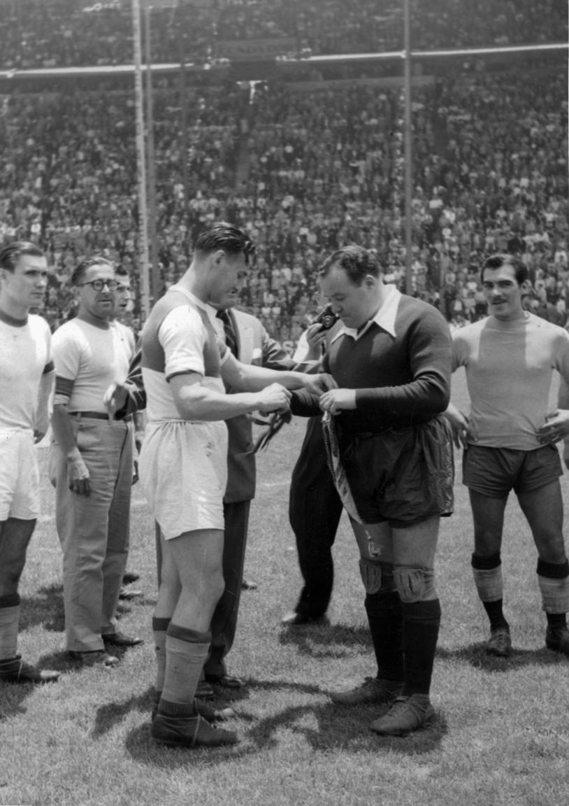 dr. Sárosi György zászlócseréje a Ferencváros mexikói túrájának egyik meccs előtt. A háttérben, szemüvegben Opata Zoltán, a csapat vezetőedzője figyel. Opata az MTK futballistája, később örökös tagja lett. Kiváló edző volt, az 1936-os, berlini olimpián a magyar válogatott szakvezetője volt és az 1952-es olimpiai bajnok magyar válogatottban Lakat Károly stábjának a tagja is volt. Lengyelországban, Jugoszláviában, Csehszlovákiában és Romániában is edzősködött.