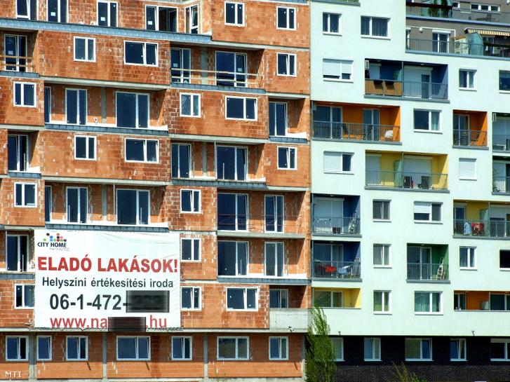 Új építésű, eladó lakásokat hirdet egy plakát egy még burkolatlan lakótömb falán, mellette egy már lakott új társasházi épület, a főváros IX. kerületében, 2013-ban.