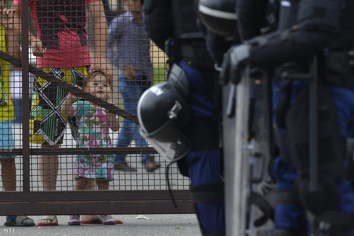 A debreceni migrációs tábor lakói nézik a tábor bejáratánál felsorakozó rendőröket 2015. június 29-én.