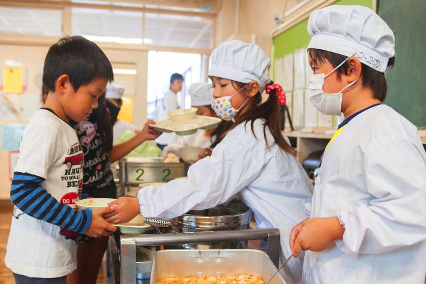 A japán diákok nem vihetik saját ételüket az iskolába. A menza kötelező, és maguk a gyerekek osztják ki az ételt. Az ebédet a gyerekek az asztaluknál fogyasztják el. A japán diákoknak kötelezően az utolsó morzsáig minden falatot meg kell enniük akkor is, ha épp nem kedvükre való az étel.
