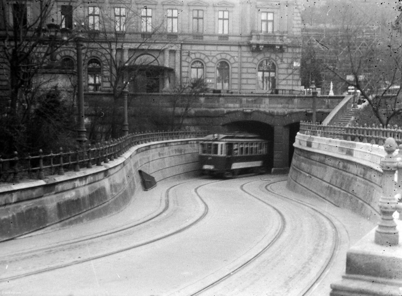 A budai oldalon viszont már jóval hamarabb, 1907-ben elkészült az alagút, mégpedig a villamos kedvéért. Igaz, ez az átjáró tulajdonképpen nem a híd alatt megy át: éles kanyarokkal kerülték ki annak lehorgonyzását. Persze ez abban az időben, amikor egyetlen, rövidke kocsiból állt a jármű, nem okozott gondot. A képen épp a déli oldalon fordul be egy villamos a tér alá (a jobbos közlekedésre csak két évvel később, 1941-ben tértünk át), nagyjából ott, ahol a második képen látható parkocska volt korábban. A háttérben a Kereskedelmi Minisztérium épülete áll még, amit a háború után lebontottak. A helyén ma részben a körforgalom, részben park van, na meg a 0 kilométerkő. Akinek éles a szeme, az alighanem kiszúrja azt a függőleges fehér vonalat a ház mellett, a háttérben felsejlő Váralagút előtt: az a régi 0 kilométerkő, a Patrona Hungariae szobor.
