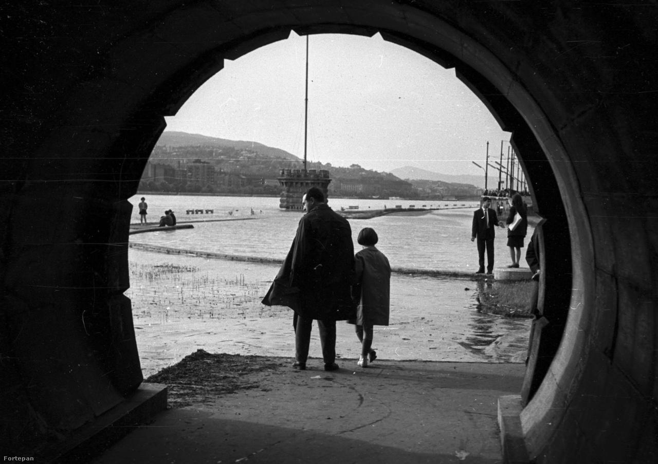 Első pillantásra olyan, mintha egy folyóba vezető csatorna torkában állna apa és gyermeke, de persze nem erről van szó. Ez a pesti rakpart gyalogos alagútja, amit néhány képpel ezelőtt még csak tervezgettek. Csak most épp odáig ért a Duna. Ez volt az 1965-ös árvíz, mely Budapesten már inkább volt izgalmas látványosság a fotó alapján, mintsem valódi veszedelem. Persze azért az ország más pontjain nem volt ilyen vidám a helyzet.