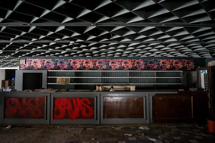 A hajdani recepció. A pultot díszítő graffiti viszonylag friss, a felette látható orchideás tapéta azonban még eredeti. A pult mögött a teljes falat elfoglalták a szobakulcsok számozott fakkjai.